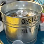 A bucket with the words 'oyster shells' sits atop a vendor table filled with shells and ice.
