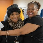 Vonda Pommills being hugged by a thankful tenant at a winter warm up charity event.