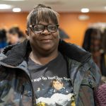 Lady smiles as she receives her winter coat from New Neighborhoods charity event in Stamford Connecticut.