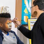 Alicia Cobb paints a child's face after he received his free winter coat at the Martin Luther King Jr apartments from New Neighborhoods Incorporated.