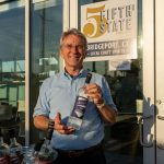 5th State Distillery owner holding a bottle of Asylum Gin