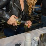 A woman pouring a shot of Suntory Whiskey